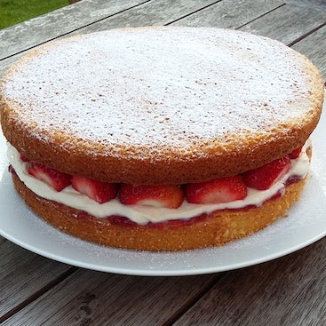 Picture of a Victoria sponge cake with strawberries and cream filling