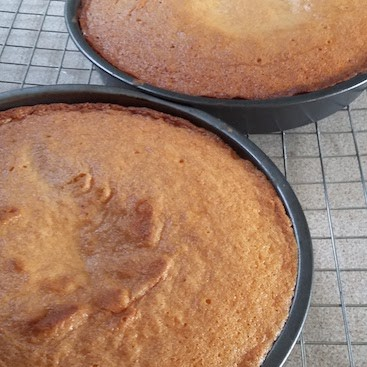 Picture of two cakes in tins with dents in the centre where they sank
