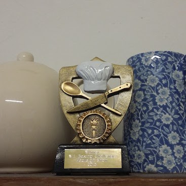 Picture of the prize winning Victoria sponge trophy on the mantelpiece between teapot and flowery jug