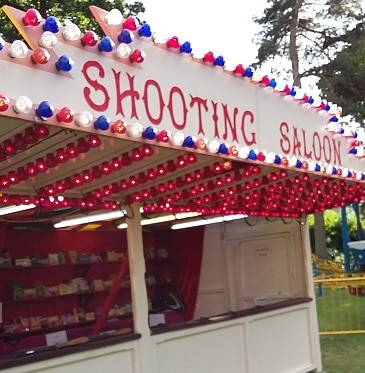 Picture of a shooting saloon rifle range at a fair, to illustrate a post on high interest current accounts