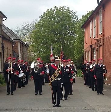 Picture of the brass band, complete with uniforms, red berets, gilded embroidery, tubas and trumbones for the parade of beavers, cubs, scouts and explorers on St George's Day in Long Melford.