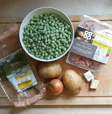 Photo of ingredients for frugal ham, mint and pea soup laid out on a chopping board - yellow-stickered mint, onion, couple of potatoes, couple of stock cubes, frozen peas and cut price ham hock