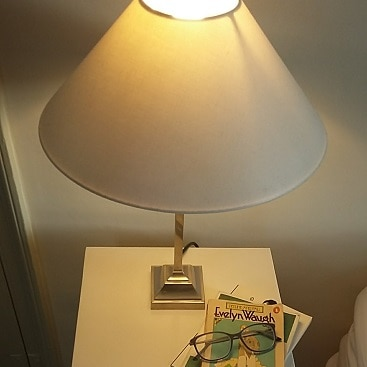 Picture of cream bedside lamp on cream bedside table with carefully arranged books to illustrate switching electricity provider to Octopus energy