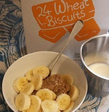 Picture of couple of Morrisons Savers Wheat biscuits, value range equivalent of Weetabix, in a bowl with a chopped banana and skimmed milk in a measuring jug, as my first breakfast on a frugal WeightWatchers diet