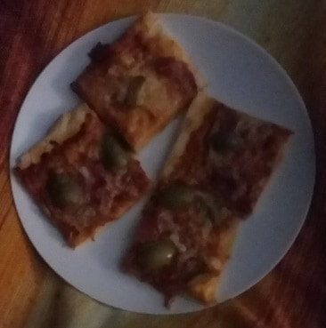 Blurry and dark picture of four slices of pizza on a plate, none of which is remotely Weightwatchers diet friendly