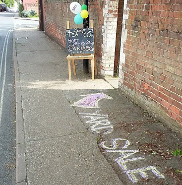 Picture of balloons, a blackboard and big chalk letters on the pavement saying yard sale
