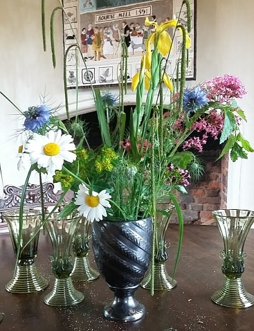 Picture of a bunch of flowers in on a table inside Bourne Mill, a National Trust property we visited on a frugal trip
