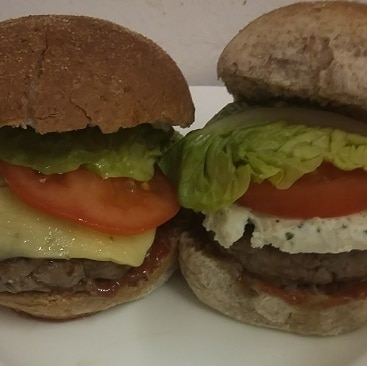 A close up picture of two beefburgers made with frugal yellow-stickered ingredients, one with cheddar and one with boursin