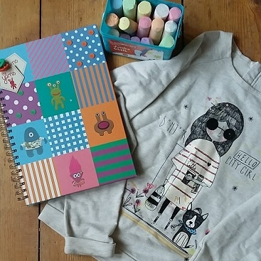 Picture of a notebook, pavement chalks and top I bought for my daughter from Hadleigh charity shops