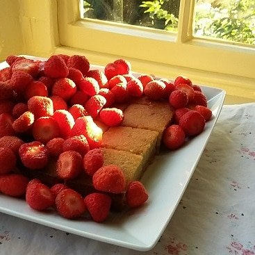 Picture of home-made banana cake piled high with Suffolk strawberries, using a quick and easy frugal recipe for banana cake to cut costs and cut food waste