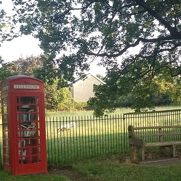 Picture of the telephone box and bench by the main street field. Activities for children should be considered when moving to the country.