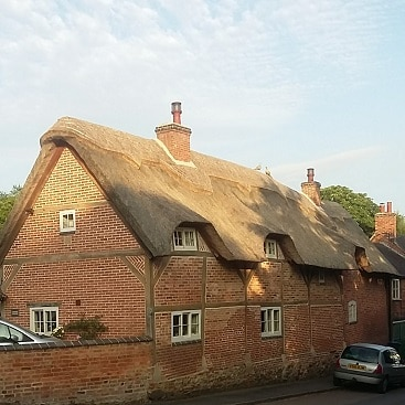 Picture of a cottage with a thatched roof, which used to be corrugated iron. Pretty houses can be a big draw when moving to the country.
