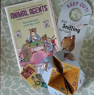 Photo of loot from the Animal Agents Summer Reading Challenge at our local library including a booklet, door sign, key ring and folding paper question and answer game, all completely free