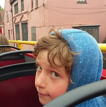 Picture of my son as the City Sightseeing bus drove past the medieval Muscian's House in Norwich, part of #lettheadventurebegin with Greater Anglia