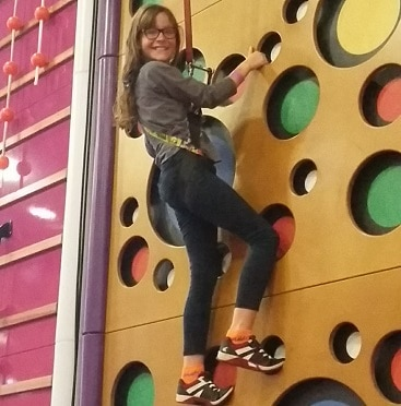 Picture of my seven year old on the climbing wall at Gravity trampoline park in Norwich, as part of the Greater Anglia #lettheadventurebegin campaign