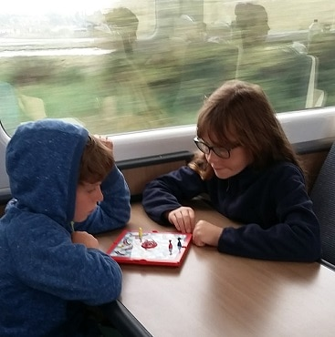 Picture of my two children playing snakes and ladders during our #lettheadventurebeing train trip to Norwich