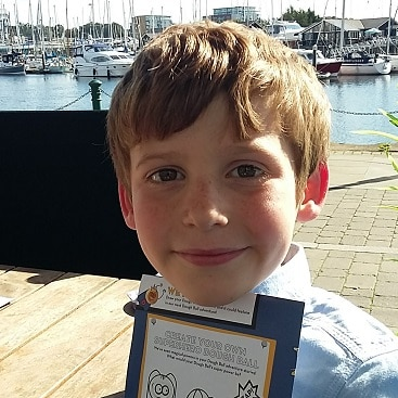 Picture of my sone with a Pizza Express activity book, sitting outside in the sunshine by Ipswich marina