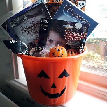 Picture of an orange pumpkin patter bucket stuffed with Halloween goodies for a frugal family movie night including Addams Family Values and Casper DVDs