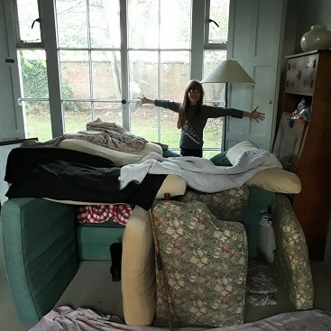 Picture of my daughter and den she built from sofa cushions and blankets