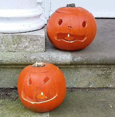 Picture of two pumpkin lanterns on our front door steps