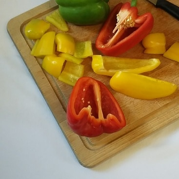 Picture of a chopped up yellow, red and green peppers on a chopping board, for my post on 80+ ways to save money on food shopping