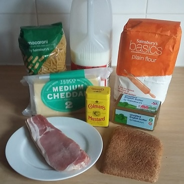 Picture of ingredients for mega macaroni cheese, including macaroni, milk, plain flour, cheddar, mustard powder, bacon, bread