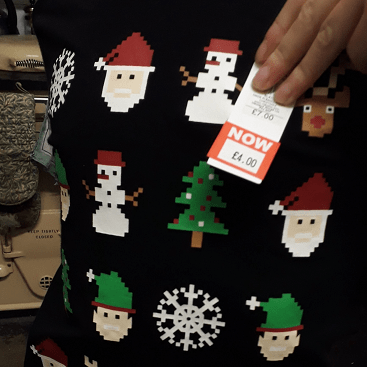 Picture of a Christmas T shirt with a price sticker showing it reduced from £7 to £4.