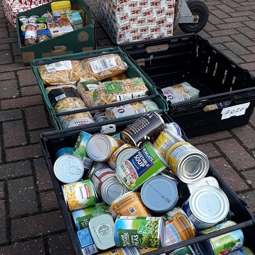 Picture of boxes of food, including pasta, tinned peas and tinned sweetcorn