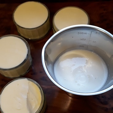 Picture of butter in glass pots plus buttermilk in a measuring job after I made butter