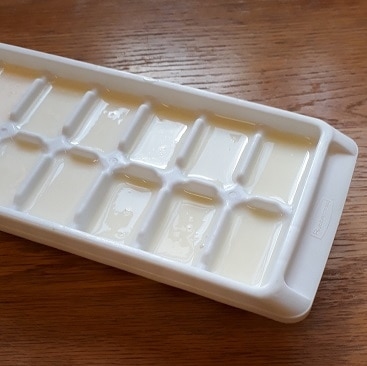 Picture of buttermilk poured into an ice cube tray, so I can defrost smaller portions when needed, after I made butter from cream.