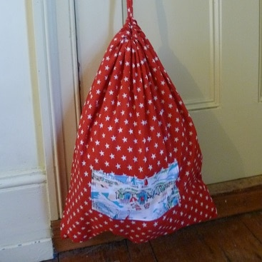 Picture of a red cloth bag instead of a plastic bag, as one way to use less plastic