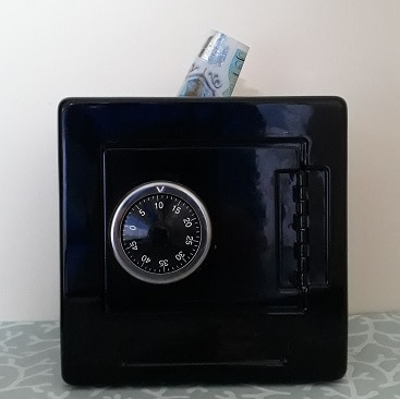Picture of a safe money box with a five pound note sticking out of the top to illustrate a post on how to save despite yourself