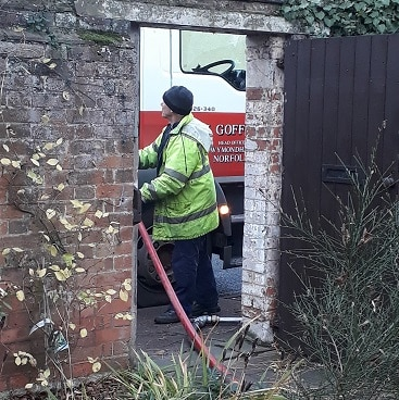 Picture of the oil delivery man checking the hose from his van through our front gate