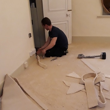 Picture of the carpet fitter fitting our new bedroom carpet, an unusual expenditure during December