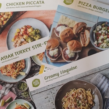 Picture of 4 Hello Fresh recipe cards, for chicken piccata, pizza burgers, asian turkey stir fry and creamy linguine, after I won a free box of food from Hello Fresh