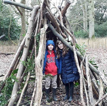 Picture of my two children in a den they built from branches and ferns at Ickworth House