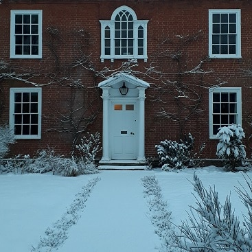 Picture of the front of our house with the garden covered in snow