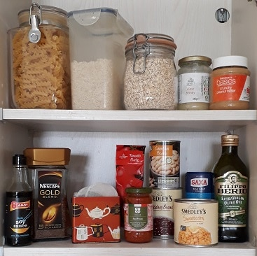 Picture of cans of food, tea, coffee, pasta rice and other essentials for an emergency food stockpile on my kitchen shelves
