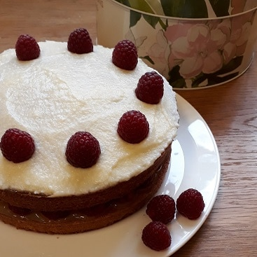 Picture of a lemon cake decorated with lemon buttercream icing and raspberries for Mothers' Day