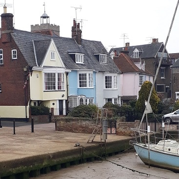 Picture of Wivehoe waterfront with a boat and pastel coloured cottages