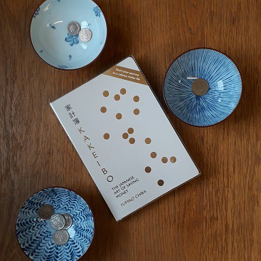 Picture of the book Kakeibo, The Japanese Art of Saving Money by Fumiko Chiba plus some bowls with money in them
