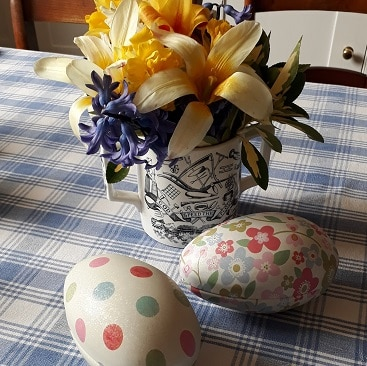 Picture of a couple of tin egg boxes and a bunch of flowers on Easter Sunday