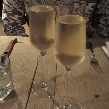 Picture of my husband behind two glasses of fizz