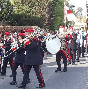 Picture of the brass band at the St George's Day parade, including the bass drummer wearing a leopardskin tunic