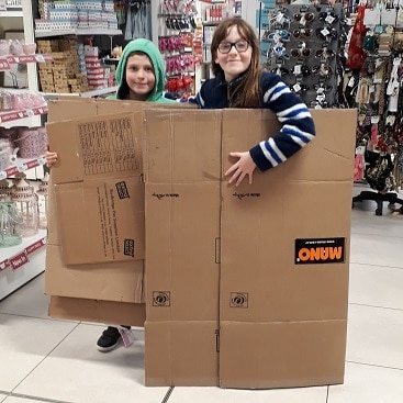 Picture of my two with cardboard boxes for my post on how to entertain kids for less