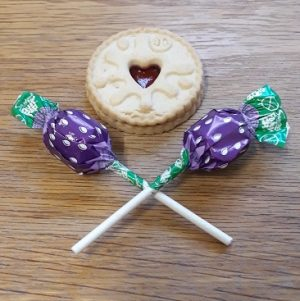 Picture of a jammy dodger and two lollipops used to bribe my daughter to eat her food for my five frugal things post
