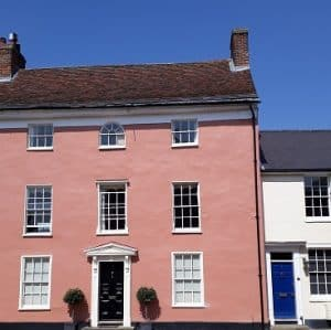 Picture of a big pink house and little white house to illustrate my post on the costs of buying a house