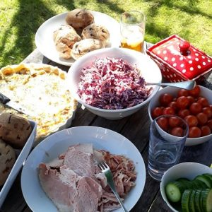 Picture of lunch on a table outside, with ham, baked potatoes, coleslaw, quiche, cherry tomatoes and cucumber