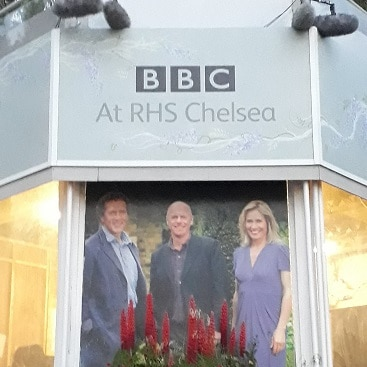 Picture of the BBC TV point at Chelsea Flower Show, with a photo of Monty Don, Joe Swift and Sophie Raworth