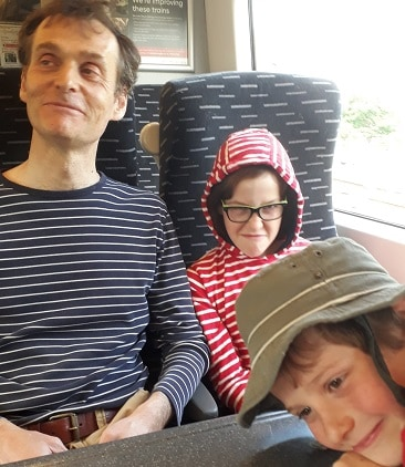 Picture of my husband looking away, my daughter looking cross and my son photobombing during our railadventure to Cambridge